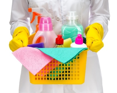 A person in a white jacket and yellow gloves, holding a box of cleaning supplies