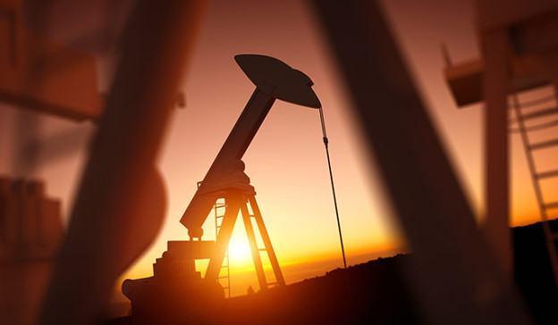 Oil rocking pump silhouetted by a sunrise