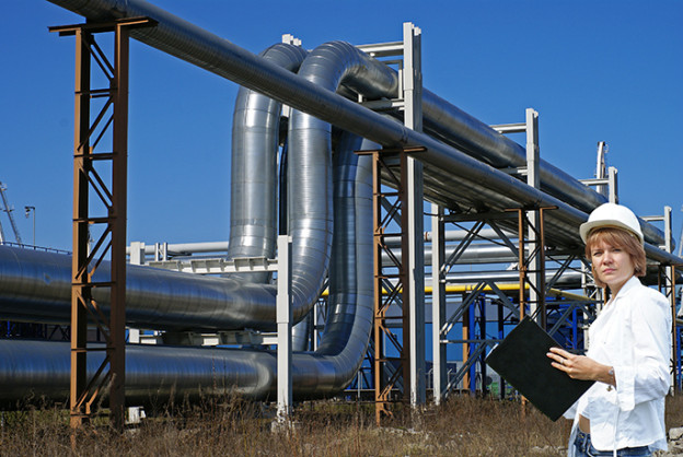 Woman standing in front of oil pipes